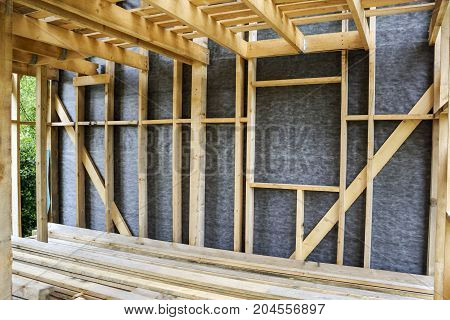 Frame of a wall and a ceiling of a wooden house vapor barrier partially sheathed walls