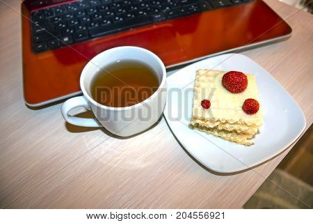 A cup of tea a piece of a wafer pie with strawberries a laptop. Lunch at work