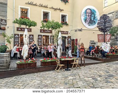LVIV UKRAINE - JUNE 29: Men and women dancing in pairs in a street cafe in Lviv on June 29 2017 in Lvov Ukraine