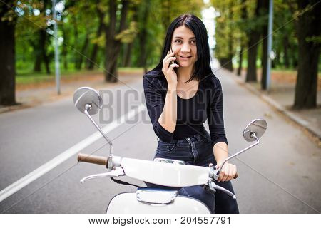 Young Happy Woman Talking Mobile Phone On Scooter