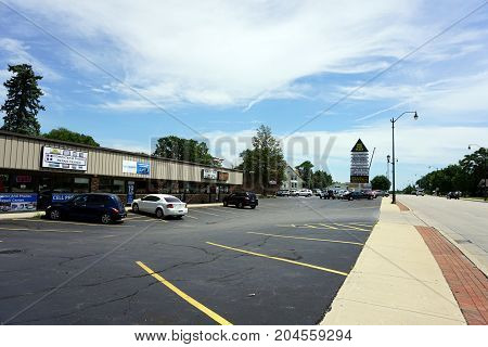 JOLIET, ILLINOIS / UNITED STATES - JULY 21, 2017:  The Pine Tree Plaza houses Zelmo's Bar and Grill, Wolf's Fine Line Tattoo, and the Computer and Phone Repair Center, on Plainfield Road.