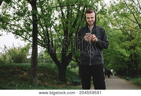 A portrait of a young guy standing in the middle of the road in this beautiful day. He is checking his playlist to be sure that only the best music is playing for the exersice. Cut view