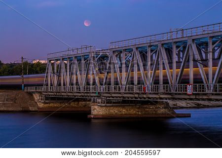 Train is passing through railway bridge, long exposure. Moon eclipse on the sky