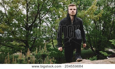 Well-trained jogger is standing on the top of the ground with one leg and looking straight forward. His sight is serious and confident. He is ready to take apart in new challenge. Close up