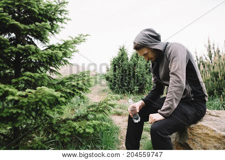 Another picture of a young jogger sitting on the stone and resting after the long-distance run. He is holding a bottle of water in his right hand. The guy will sit some more time and then start to jogging again.