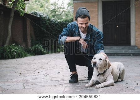 The ideal picture of a guy and his best friend - the golden labrador. The dog is laying on the ground while his owner is stroking a dog on the head. This gus is happy to be with his pet and smiling because of that.