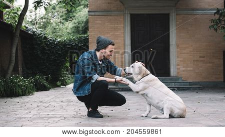 A guy is squatting near the golden labrador at the backyard in a beautiful bright day. He is holding the dog's paw in his right hand while stroking on the animal's head with left hand. The guy is smiling to his best friend. THis picture is magical