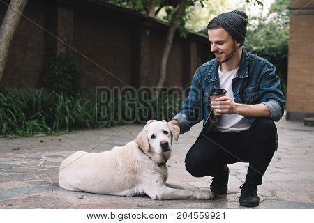 A handsome and cheerful guy is squatting near the big dogs at the backyard in a gorgeous and bright day. He is holding a cup of coffe in one hand and stroking on the dog's head with the other one. And the animal likes it. Close up