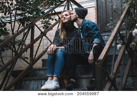 THe portrait of two people sitting together at stairs. THe guy is kissing the girl in the chic and embracing her. She is enjoying the kiss and dreaming good things.