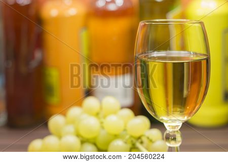 A glass of white wine and a bunch of grapes