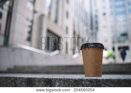 A picture of a cup of coffee that was left on the concrete steps near the office building by a businessman. This cup is nice and brown. This cup of coffee is still warm. Close up