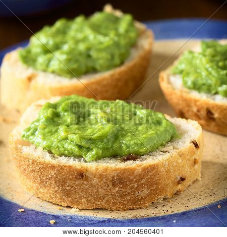 Fresh avocado cream or guacamole on onion bread slices photographed with natural light (Selective Focus Focus on the front of the avocado cream on the first bread)