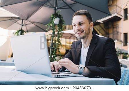 Close up of a young businessman sitting at the table and working on laptop. He has a business meeting starting some time ago. Maybe it will bring good advantages for him
