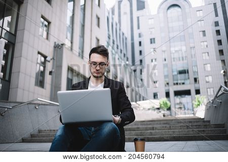 The businessman is sitting on the office building's steps and working on his laptop. He took a cup of coffe with him and put it on the groud beside him. The guy looks very serious, attentive and smart.