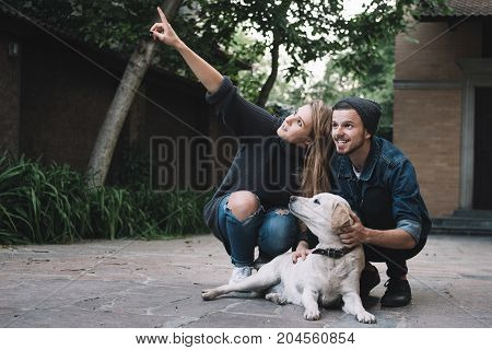 A perfect picture of young couple squatting near a pet at the backyard. Girl is pointing on something and looking to that direction. A guy is looking there to the same thing. They both are smiling. The golden labrador is beside young people