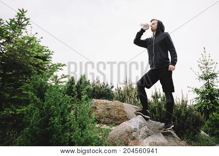 The picture of a runner standing almost at the top of a hill and resting. He decided to drink some water and then continue his exercises. The runner is almost ready to go on.