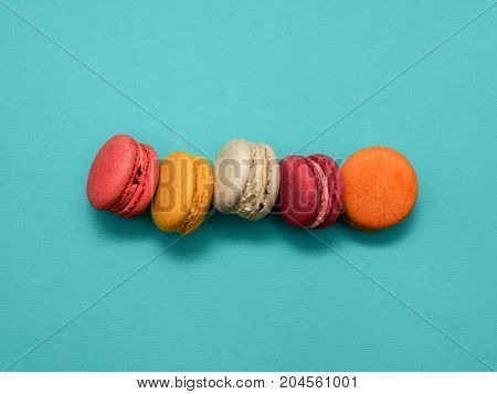 Macaroons Top view Five sweet and colorful macaroons or macaron on turquoise background French dessert Trendy bright photo background with space for text