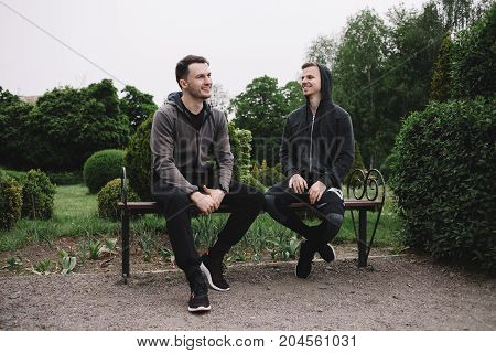 Two handsome guys are sitting together on the bench and having some rest after a long-distance marathon. He has finally reached the finish and happy to have some rest.