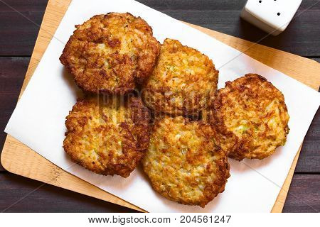 Rice patties or fritters made of cooked rice carrot onion garlic and celery stalks photographed overhead with natural light