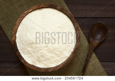 Powdered or dried milk in wooden bowl photographed overhead with natural light (Selective Focus Focus on the top of the milk powder)
