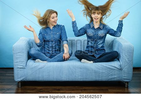 Two funny shocked women wearing jeans shirts having windblown blonde hair. Blue background.