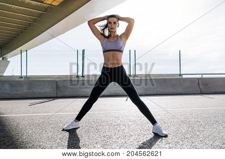 Fitness woman standing on a road, warming up her body for training