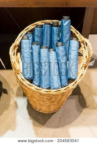 Blue Foldable Umbrellas In Wicker Basket On Cement Floor