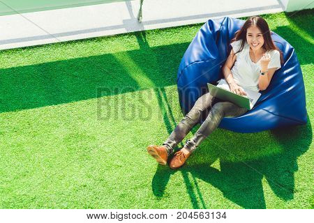 Young cute Asian girl celebrate with notebook laptop sit on bean bag in garden copy space on green grass. Success small business modern lifestyle information technology or online shopping concept