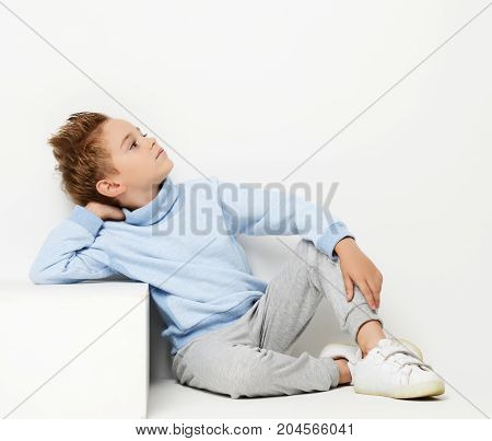 Happy young boy sitting in light blue sweater looking at the corner, positive attitude, full lenght on white background