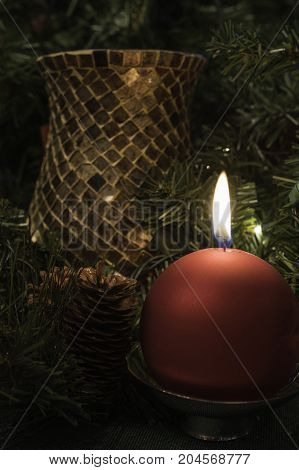 vertical Christmas decor background with red ball candle, pine cones and greenery