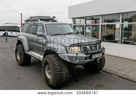 Iceland August 24 2017: Specialty all terrain vehicle with massive wide tires is parked near a gas station.