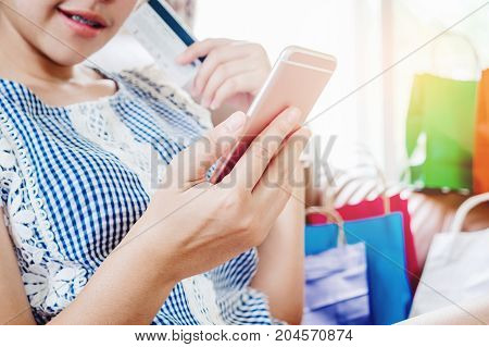Woman Shopping Online Using Smartphone With Credit Card Enjoying In Home