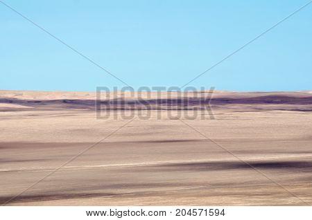 Arid lands of a desert under cloudless blue sky