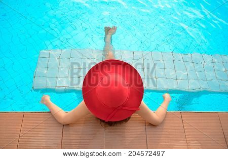 Young woman happy in red big hat relaxing on the swimming pool travel near the sea and beach. Summer Concept