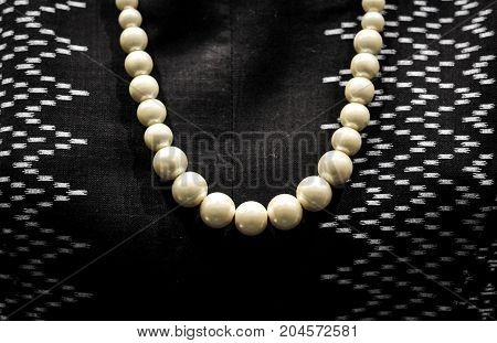 Pearl necklace on the dress background, A traditional hand-weaving loom being used to make Thai silk cloth, Thailand Household handicrafts of Thai silk