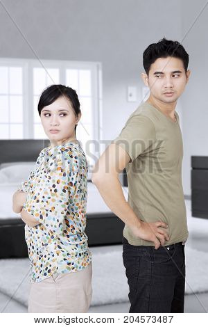 Portrait of young couple ignored at each other after quarreling in the bedroom