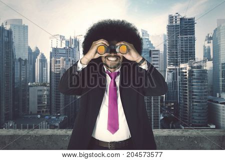 Image of happy young businessman standing in the skyscraper while using a binocular for looking an opportunity