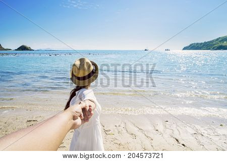 Back view of Asian woman holding hand of her boyfriend while leading to the beach