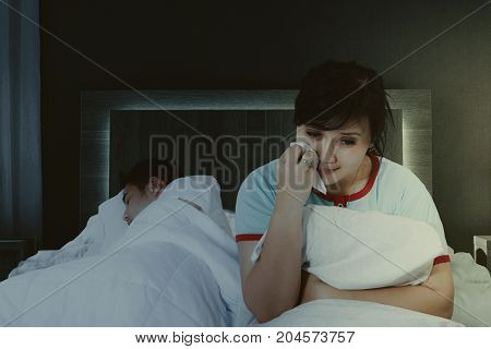 Picture of depressed woman having insomnia while sitting with her asleep husband in the bedroom