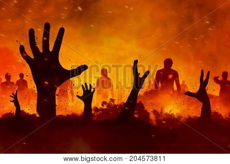 Halloween concept scary zombies hand silhouette on fire background