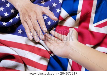 Symbolizing of peace. Hand of United states offering a help with hand of England