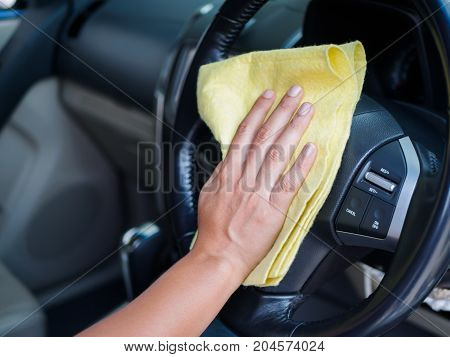Hand cleaning interior car steering wheel with microfiber cloth.