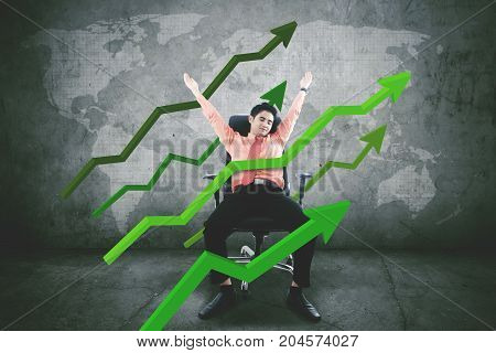 Image of young businessman dreaming his success with upward arrows while sleeping on the chair