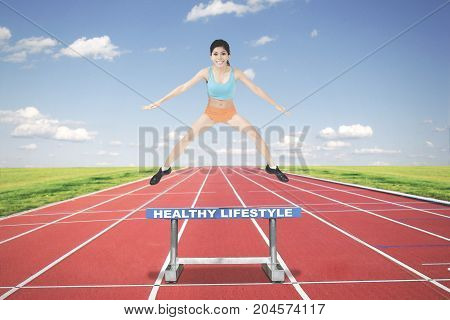 Picture of a sporty woman running on track while jumping above a text of healthy lifestyle on the hurdle