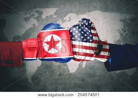 Concept of conflict. Two hands wearing boxing gloves with North Korea and USA flag