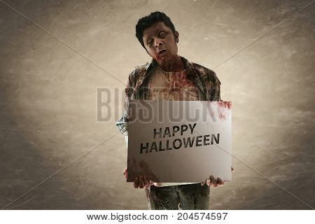 Halloween concept scary zombie holding halloween paper
