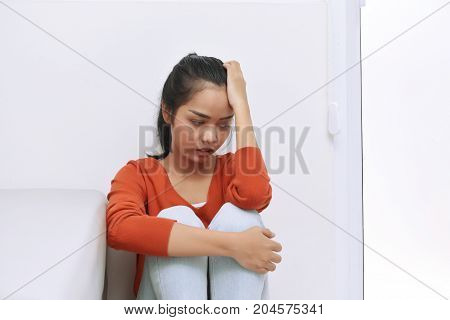 Young Asian Woman Sitting On The Floor And Feeling Lonely