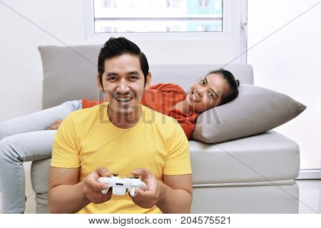 Happy Asian Couple With The Woman Lying Down On Couch And The Man Playing Video Games