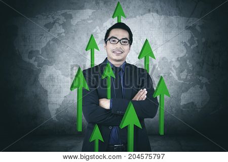 Image of young businessman looks confident while standing with upward arrows