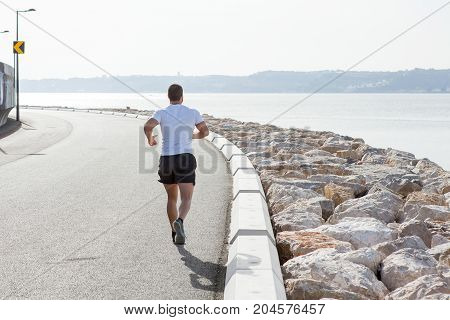 Young strong man wearing sportswear and running on seaside road with sea in background. Back view.